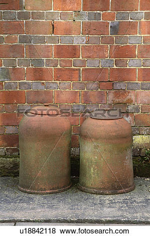Pictures of Close up of terracotta rhubarb pots in front of brick.