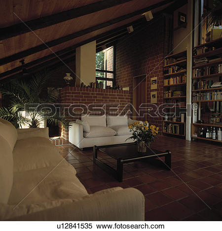 Stock Image of White sofa against brick wall in eighties.
