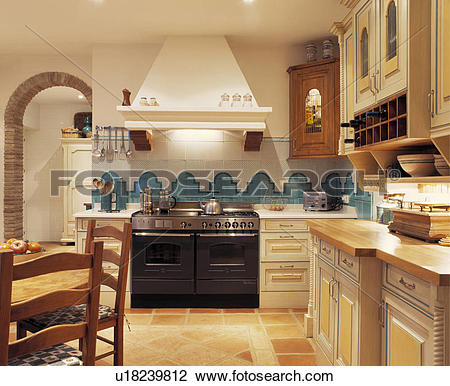 Stock Photo of Turquoise and white wall tiles above black range.
