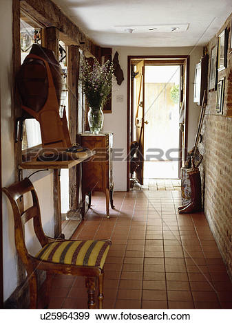 Stock Photograph of Terracotta floor tiles in narrow country hall.
