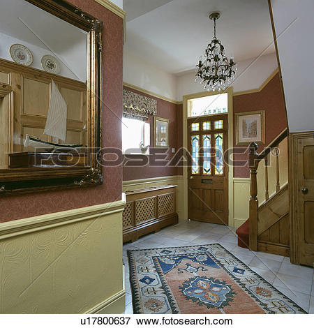 Stock Photography of Patterned rug on terracotta floor tiles in.