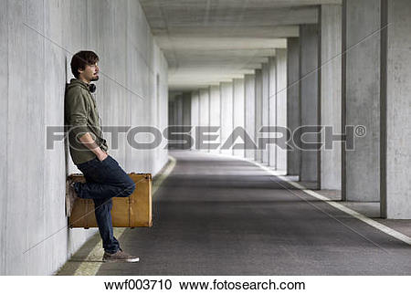 Stock Photography of Man with leather suitcase waiting in a car.
