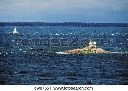 Stock Photography of Sailboat passing small house isolated on tiny.