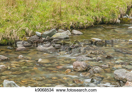 Stock Photo of Small stream over rocks with a grass bank k9068534.