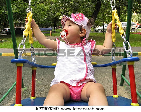 Stock Photograph of Small child rides on the chain swing k27803249.