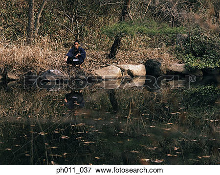 Picture of Samurai warrior squatting at the edge of a pond.