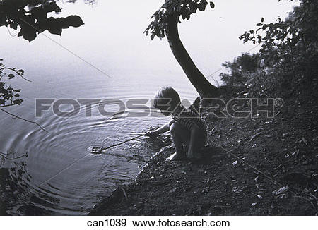 Stock Photograph of B/W 6yo boy playing with stick at the edge of.