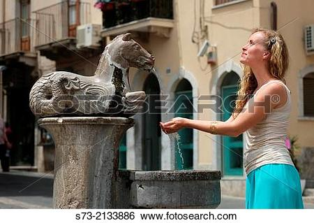 Stock Images of Woman in the Horse drinking fountain outside.
