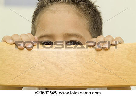 Stock Image of Child hiding behind a chair x20680545.