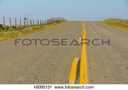 Stock Photography of Middle of a county road with a barbed wire.