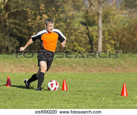 Stock Photography of Soccer player passing a slalom course.