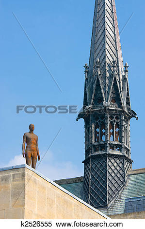Stock Image of Antony Gormley statue next to the spire of Exeter.