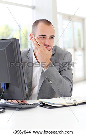 Stock Photo of Businessman in front of desktop computer with.