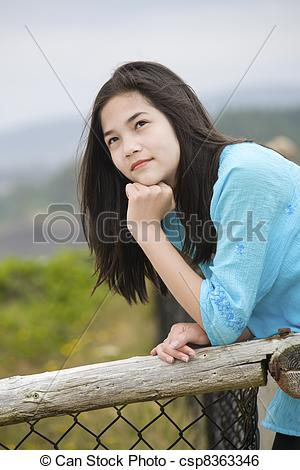 Stock Image of Preteen biracial girl by ocean shore with a.