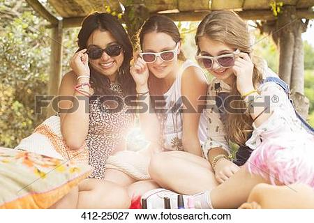 Picture of Portrait of three teenage girls wearing sunglasses and.