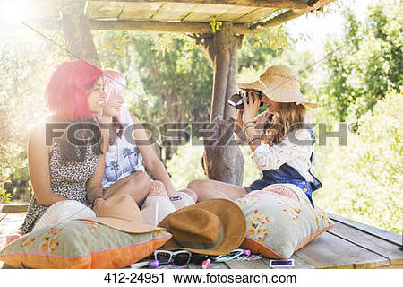 Stock Photography of Three teenage girls taking photos in tree.