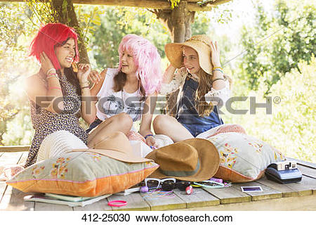 Stock Photography of Three teenage girls wearing wigs and hat.