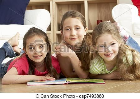 Stock Photography of Three Young Girls Reading Book at Home.