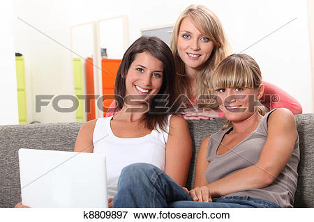 Picture of Three girls relaxing at home in front of laptop.