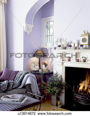 Stock Photo of Mauve living room with patterned throw on sofa.