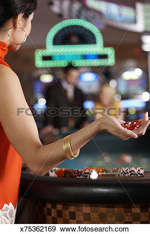 Stock Photograph of Asian woman about to throw dice at Craps table.