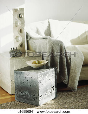 Stock Photography of Concrete sculpture and cube table beside sofa.