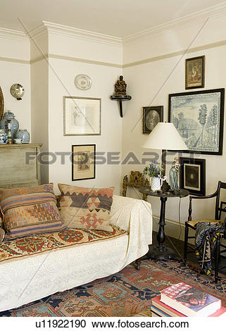 Stock Photography of Kelim cushions and cream throw on sofa in.