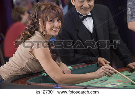 Stock Photography of Dealer and woman about to throw dice at craps.