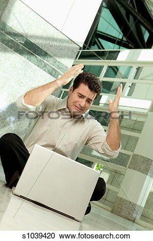 Stock Photography of Frustrated businessman sitting on floor with.