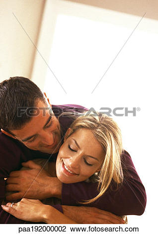 Stock Photo of Man hugging woman from behind, head and shoulders.