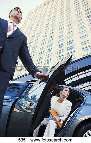 Stock Photography of Chauffeur opening car door for businesswoman.