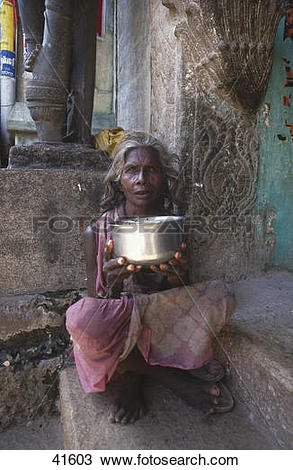 Stock Photo of Female beggar sitting at entrance of temple.