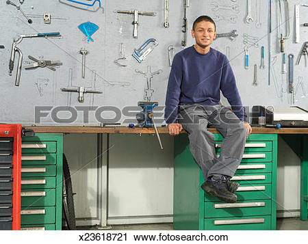 Stock Photography of Young man sitting on a workbench in front of.