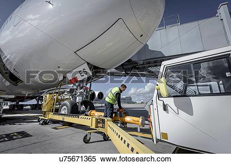 Stock Image of Ground crew attaching tow bar to A380 aircraft.
