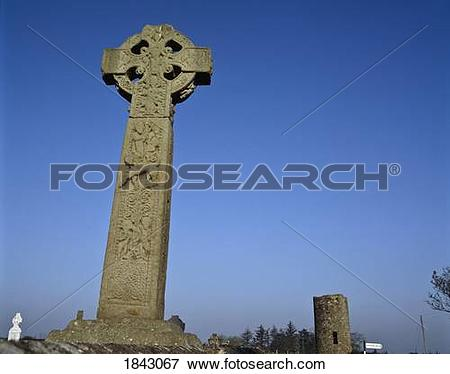 Picture of Celtic Cross In A Burial Ground With A Round Tower In.