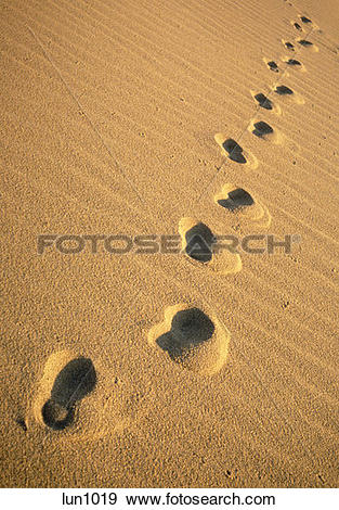 Stock Photograph of Single set of footsteps tracks across the sand.