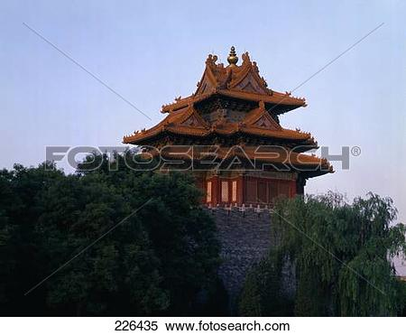Stock Image of Trees in front of traditional building against blue.