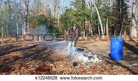 Pictures of A man working a burning pile of trash and debris along.