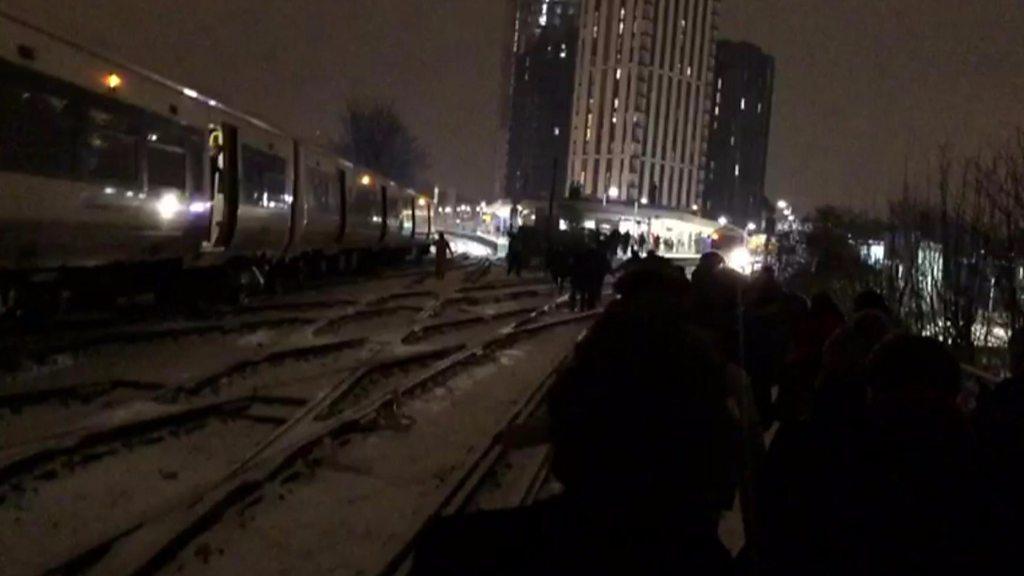 Frustrated passengers walk on tracks near Lewisham.