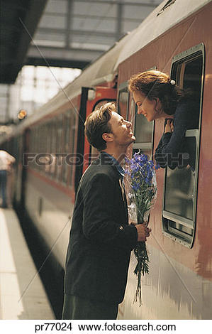 Stock Photo of Woman leaving on train, man holding flowers.