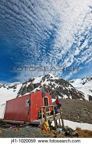 Stock Photograph of Tramper outside Barker hut as high cloud forms.