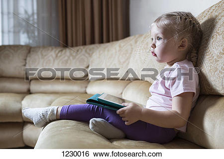 Stock Images of Transfixed girl on sofa with digital tablet.