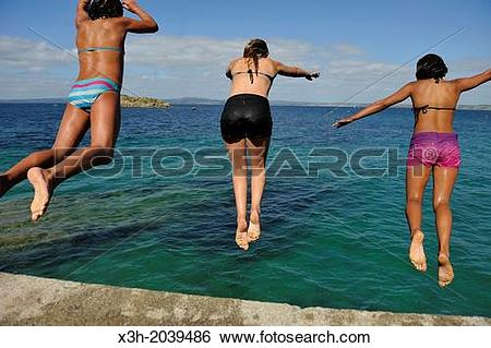 Stock Images of teenagers diving from the top of a sea wall at.