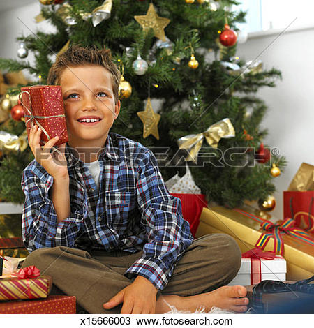 Stock Photo of a young boy sitting near a christmas tree holding a.