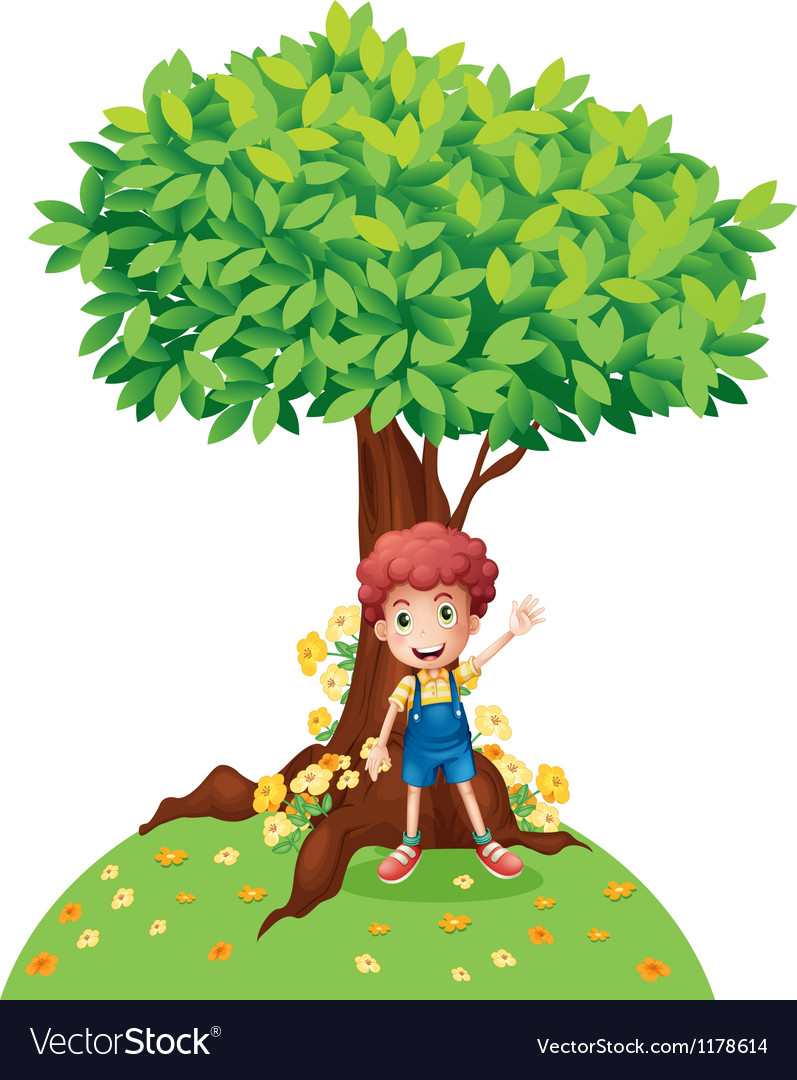 A young boy standing under a big tree.