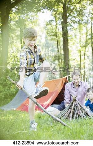 Stock Photo of Boy breaking stick for campfire with father and.
