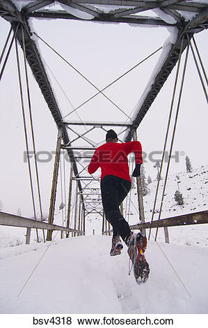 Pictures of A man running across a tressel brigde on a snowy day.