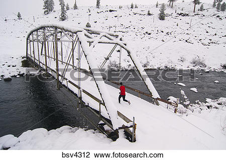 Stock Photo of A man running across a tressel brigde on a snowy.