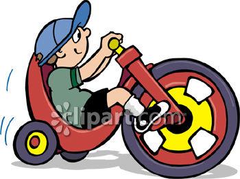 Little Boy Riding a Plastic Big Wheel Trike.
