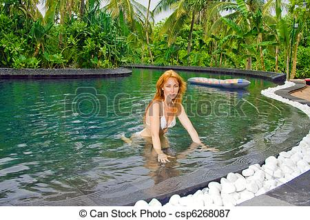 Picture of Young pretty woman in pool in tropical garden.